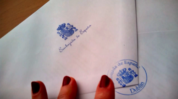 Video still of the artist submitting the application to reject her citizenship in Dublin. The authorities opened the envelope, read it and ordered her to go upstairs to the office of the consul. Afterwards they refused to send the letter to the Spanish Government, so she sent it directly by registered mail © Núria Güell: Stateless by Choice. On the Prison of the Possible, 2015–2016