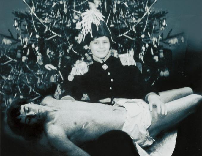 Karácsonyfa előtt álló, katonaruhát viselő gyermek El Kazovszkij, kezében fekvő, ágyékkötőt viselő, felnőtt férfi.  Őrzési hely: El Kazovszkij hagyatéka